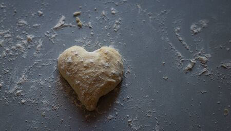 heart shaped Bread dough  on floured board ,making bread rolls at home.,homemade. Banque d'images