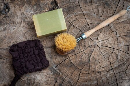 scrubbung brush with olive oil soap ,aleppo or alep soap  & and handmade tawashi,on wooden table ,zero waste.;