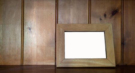 Mock up of blank  wooden picture frame on wooden counter  against wood  background.