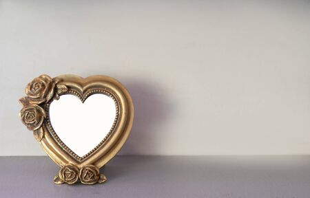 Mock up of gold heart shaped picture frame on modern counter. Banque d'images