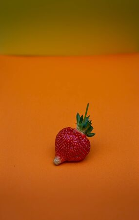 single  unperfect Strawberry on  orange background Banque d'images