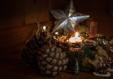 Christmas decoration ,with pine cones & a burning candle ,room for copy, Christmas card.