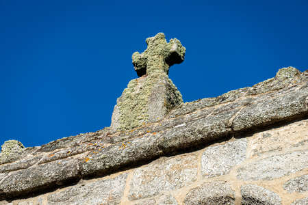 stone cross detail of old granite bell tower against blue sky, fau de peyre, lozere, france.