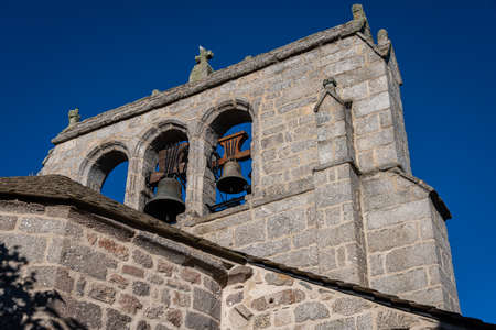 old granite bell tower against blue sky, fau de peyre, lozere, france. Banque d'images