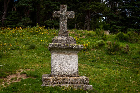 Stone cross or memorial in meadow close up, Lozere, France.