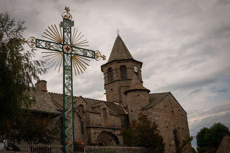 Nasbinals church with ornamental cross in forground, cloudy skys, Lozere, France.
