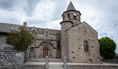 Nasbinals church with hiker on the saint james walk, cloudy skys, Lozere, France ..