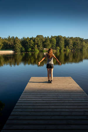 Young woman with outstretched arms standing relaxing or stretching on wooden pontoon staring at lake. evening light Back view.