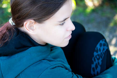 young woman, teenager sitting outside, deep in thought, relaxing. Archivio Fotografico