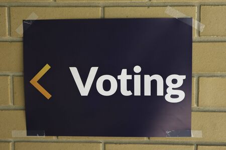 White text on blue background voting sign on cream brickwork with a yellow and orange arrow