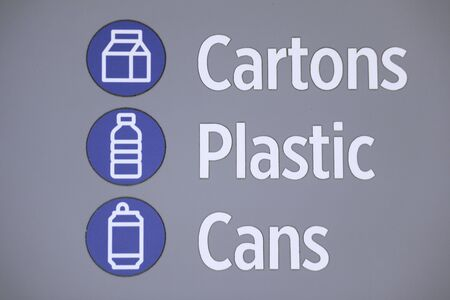 Blue and white sign with bold text. Cartons, plastic and cans with sumbolds of each Stock Photo