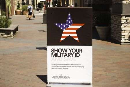 San Francisco, California /USA - June 16 2019 : Show your Military id and save sign with a American flage star on a brown background in San Francisco premium outlets mall Stock fotó - 138306295
