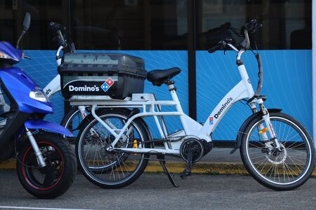 Tweed, Queensland, Australia, May 04 2019: White Dominos pizza delivery bicycle with rack and carry bag on the back in front of window