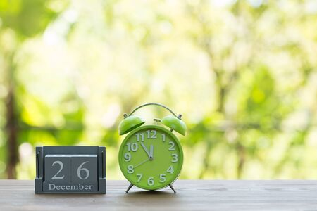 boxing day: December 26. BOXING DAY.calendar with date on wooden background.Retro alarm clock with five minutes to twelve oclock. Christmas concept