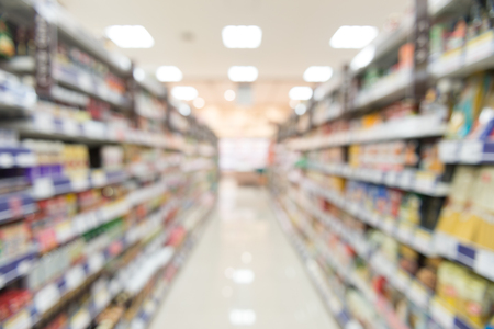 Blurry view of supermarket,Wide perspective view shelves variety of snacks, defocused blurry background bokeh light in supermarket. Business concept. Banco de Imagens