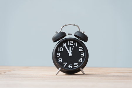 Retro alarm clock with five minutes to twelve o'clock. Archivio Fotografico