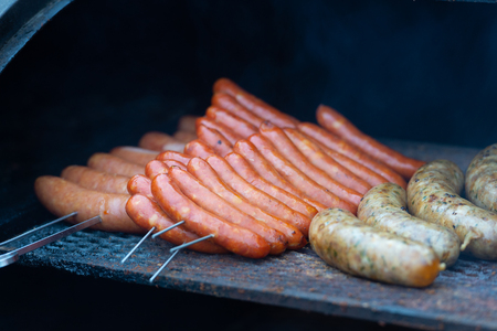 Fresh sausage and hot dogs grilling outdoors on a gas barbecue grill.