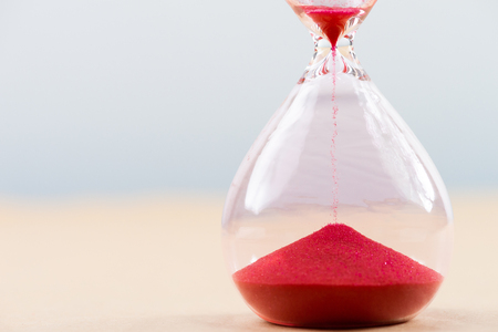 Hourglass with flowing sand on table. Time management