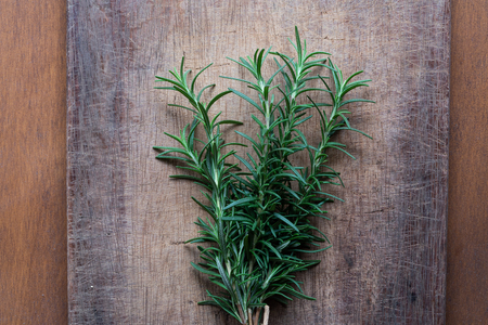 Rosemary plant on wooden rustic table from above, fresh organic herbs with copy space for text
