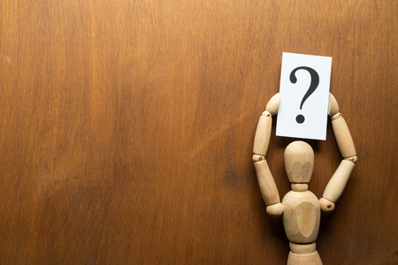 Wooden mannequin holding  in hands with  white plate with the image question mark Stock Photo