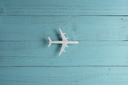 Miniature toy airplane on wooden  background. Trip by airplane.