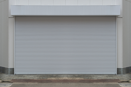Un gros plan d'une porte à enroulement métallique automatique utilisée dans l'usine, le stockage, le garage et l'entrepôt industriel. La tôle ondulée et pliable offre un gain de place et une sensation urbaine et rustique Banque d'images