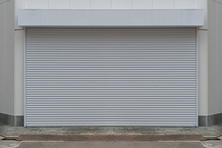 Un primer plano de la puerta enrollable de metal automática utilizada en fábrica, almacenamiento, garaje y almacén industrial. La hoja de metal ondulada y plegable ahorra espacio y proporciona una sensación urbana y rústica. Foto de archivo