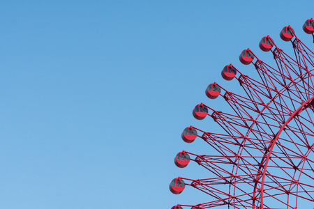 red Ferris wheel and blue sky