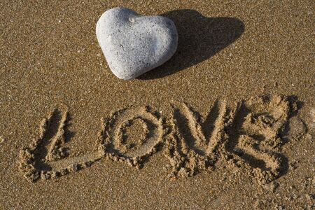 heart under: A heart shaped stone on a sandy beach with the word love under written in the sand