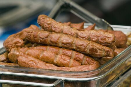 grill tongs sausage: a glass tray with barbecued sausages in it with a pair of tongs in the background