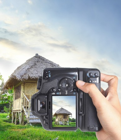 hand holding digital slr camera vertically photo