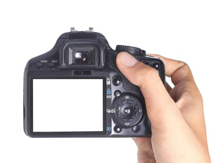 back to camera: hand holding digital slr camera