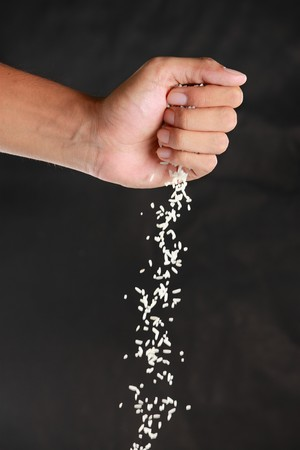 black rice: gesture of hands were dropped rice down in the black background Stock Photo