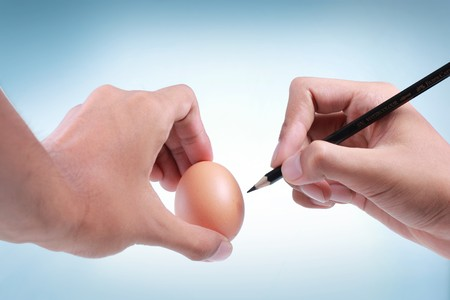 hands trying to draw  on egg photo