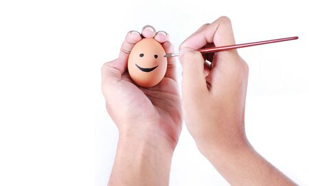 hands drawing smiley face on egg photo