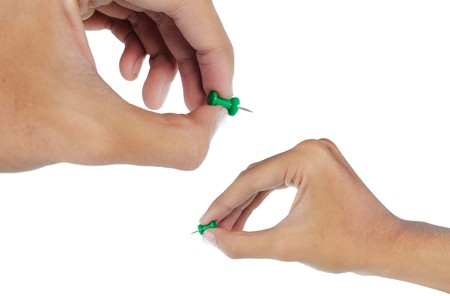hands attaching a green thumbtack photo