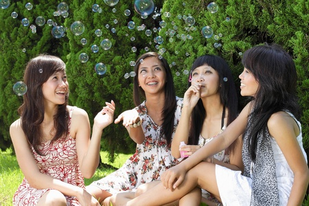 Group of diverse friends playing with bubble soap on a bright sunny day photo