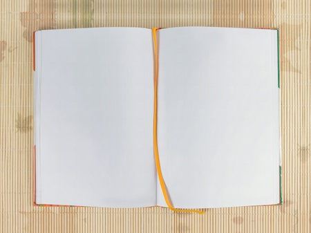 white blank open notebook over wooden background photo