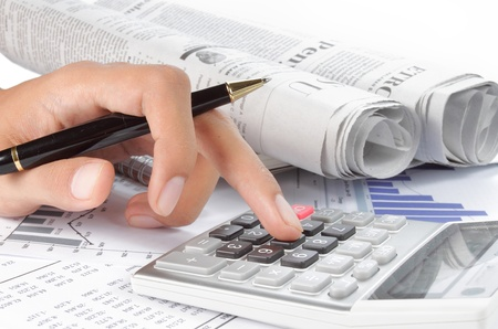 womans hands with a calculator and a pen. newspaper on a background Stock Photo