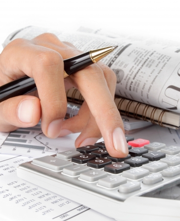 womans hands with a calculator and a pen. newspaper on a background photo