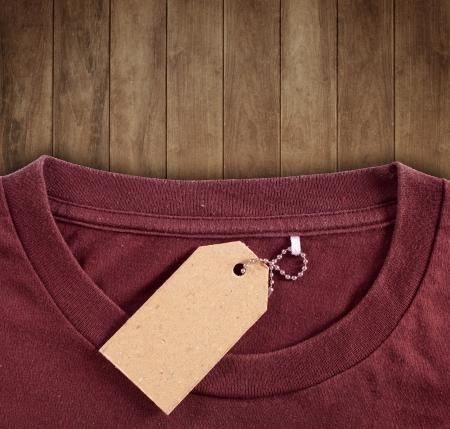 etiquetas de ropa: etiqueta de precio se bloquea en camiseta marr�n en antecedentes de madera