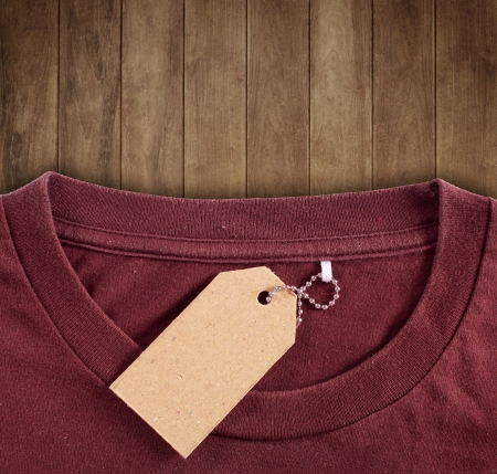 price tag hang over brown tshirt on wood backround photo