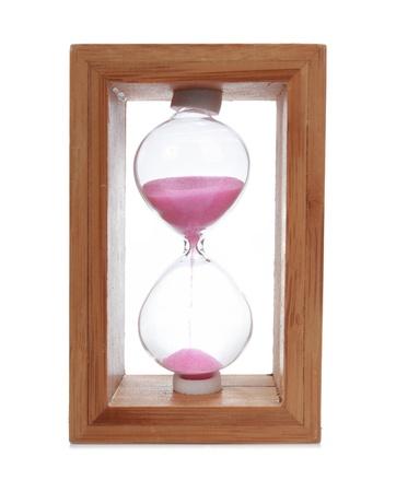 hölzerne Sanduhr mit einem rosa Sand nach unten fließt. isoliert auf weiss Standard-Bild