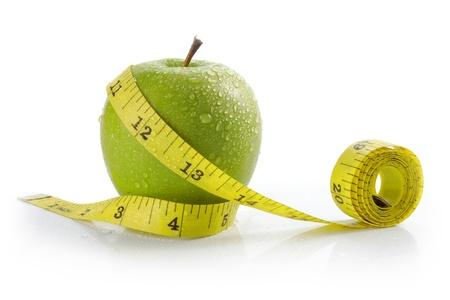 metro medir: manzana fresca con una cinta de medir. concepto de dieta, pérdida de peso Foto de archivo