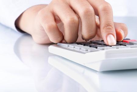Nahaufnahme von Hand mit Taschenrechner auf weißem Hintergrund