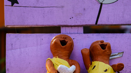 terra cotta: The Couple of terra cotta figure that shown happiness emotion on the bench