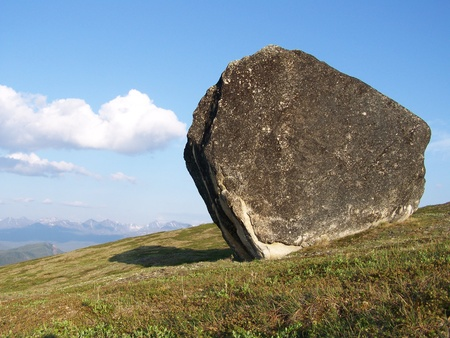 erratic: Erratic Boulder Resting on Tundra in the Alaska Range with Sky and Clouds Stock Photo