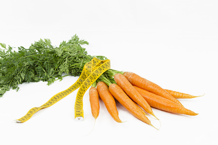 Vegetarian diet to reduce weight. A bunch of freshly picked carrots wrapped in a body measuring tape ruler which symbolizes the waistline