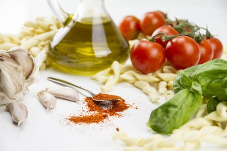 Close-up of italian typical pasta recipe: handmade durum wheat flour pasta, tomatoes, garlic, extra virgin olive oil, ground chili, parsley and basil on white background 写真素材