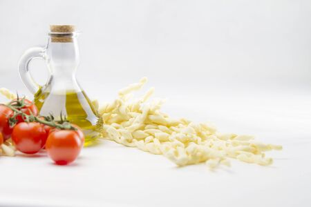 Close up still life of italian handmade pasta fusilli al ferretto with tomato puree and extra virgin olive oil on white background 写真素材